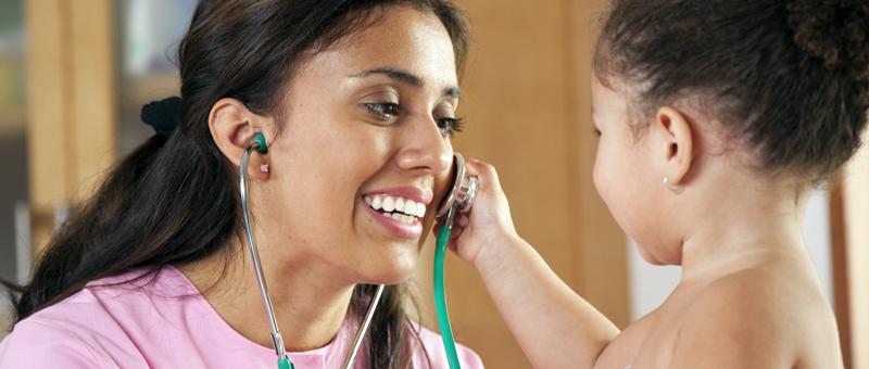 Hispanic nurse examining little girl in doctor's office
